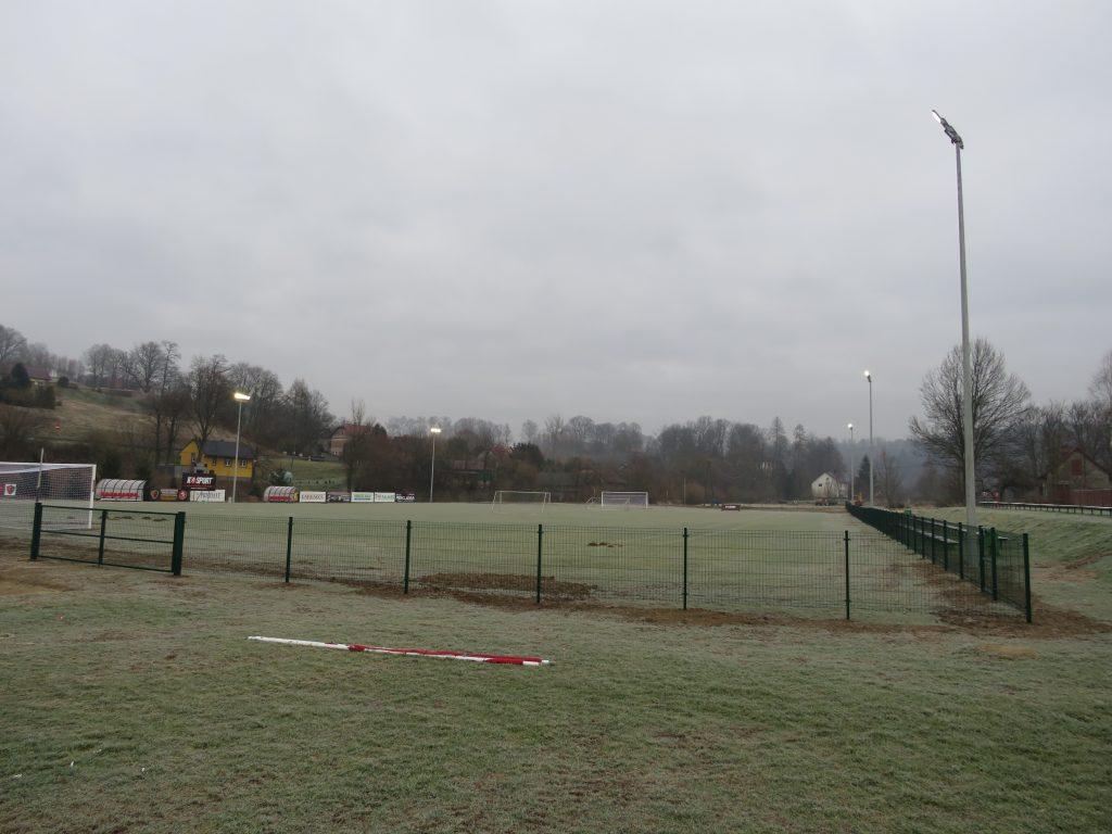 Zdjęcie przedstawiające ogrodzone i oświetlone boisko sportowe w Rzepienniku Biskupim.